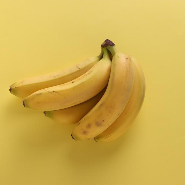 Süße bananen auf druckvollem pastellgelbem hintergrund, draufsicht, nahaufnahme Premium Fotos