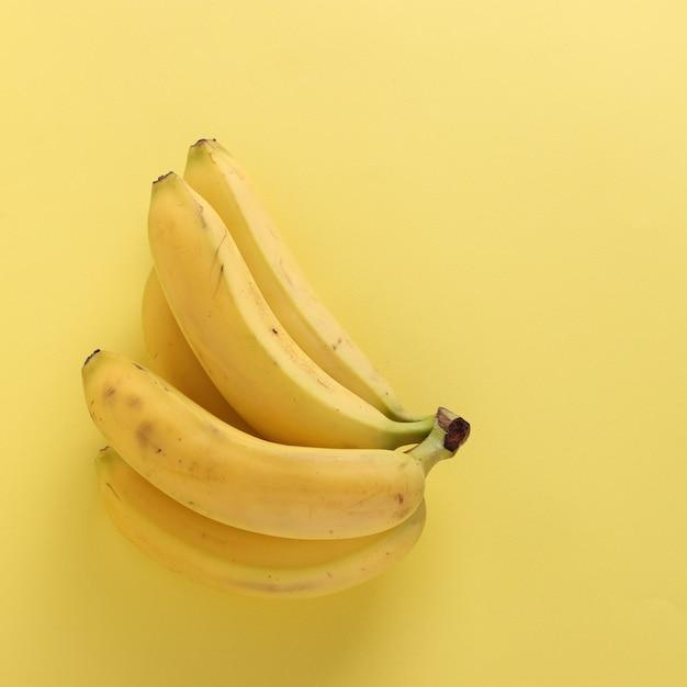 Süße bananen auf knackigem pastellgelb Premium Fotos