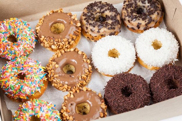 Süße donuts in einer pappschachtel Premium Fotos
