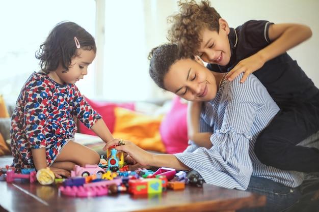 Süße familie, die mit spielwaren im wohnzimmer spielt Premium Fotos