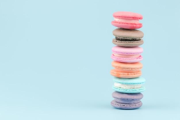 Süße französische makronen backen mit weinlesepastell gefärbtem ton auf blauem hintergrund zusammen. Premium Fotos