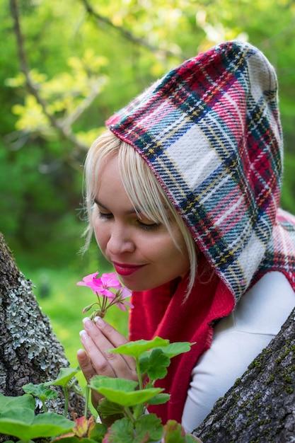 Süße frau mit kapuze im wald, das reiche aroma einer schönen rosa blume riechend. Premium Fotos