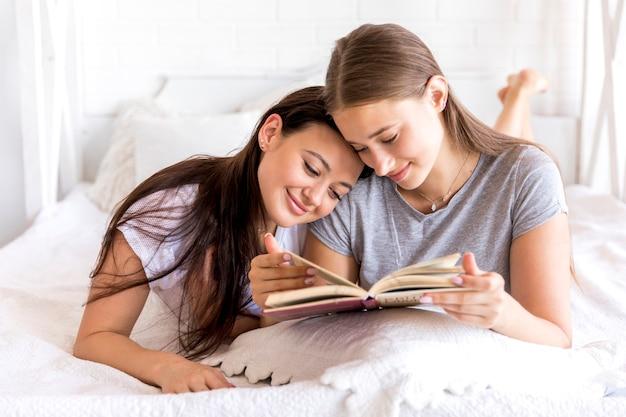 Süße frauen, die zusammen lesen Kostenlose Fotos