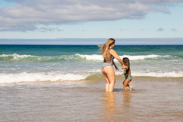 Süße junge mutter und kleine tochter, die knöcheltief im meerwasser stehen und freizeit am strand am meer verbringen Kostenlose Fotos