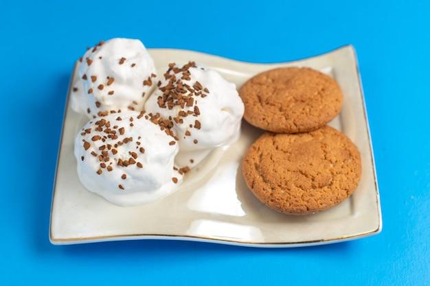 Süße kekse der vorderansicht mit köstlicher eiscreme-innenplatte auf dem blauen schreibtisch Kostenlose Fotos