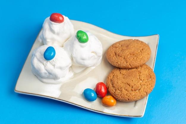 Süße kekse mit halber draufsicht und köstlichem eis auf dem blauen schreibtisch Kostenlose Fotos