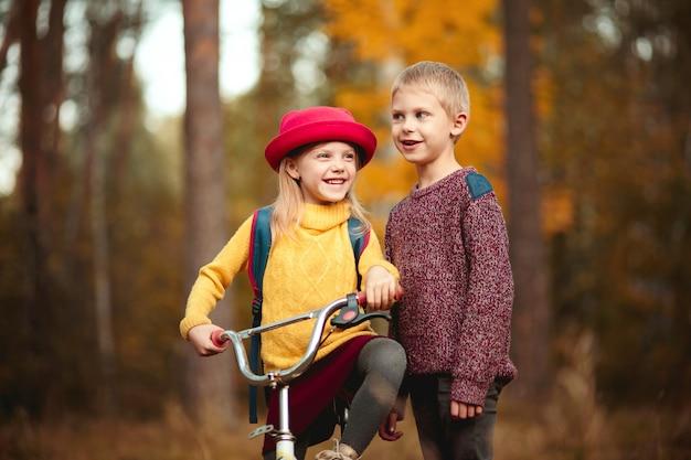 Süße kinder in bunten kleidern, bruder und schwester, gehen mit dem fahrrad im herbstpark spazieren und unterhalten sich Premium Fotos