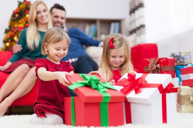 Süße kleine mädchen, die weihnachtsgeschenke öffnen Kostenlose Fotos