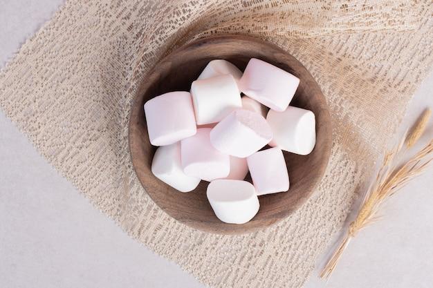 Süße marshmallows auf holzbrett auf sackleinen Kostenlose Fotos