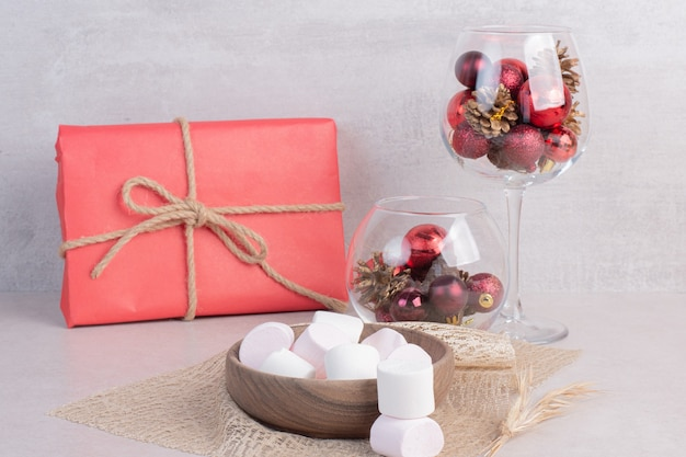 Süße marshmallows auf holzteller mit glas weihnachtlicher roter kugeln Kostenlose Fotos