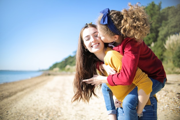 Süße mutter, die ihre tochter auf ihrem hinteren weißen gehen am strand trägt Premium Fotos