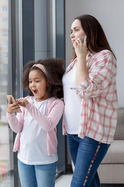 Süße mutter, die neben ihrer tochter telefoniert Kostenlose Fotos