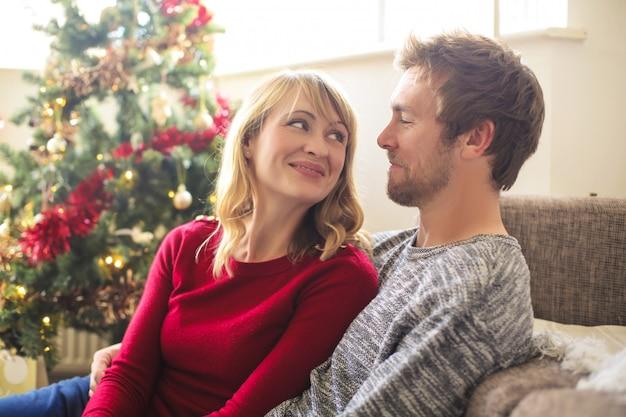 Süße paare, die im wohnzimmer, weihnachten feiernd sitzen Premium Fotos