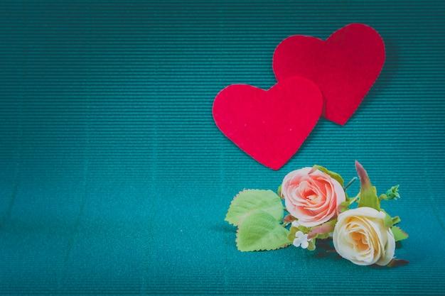 Süße rosen und 2 rote herzen auf grünem hintergrund, valentinstagkonzept. Premium Fotos