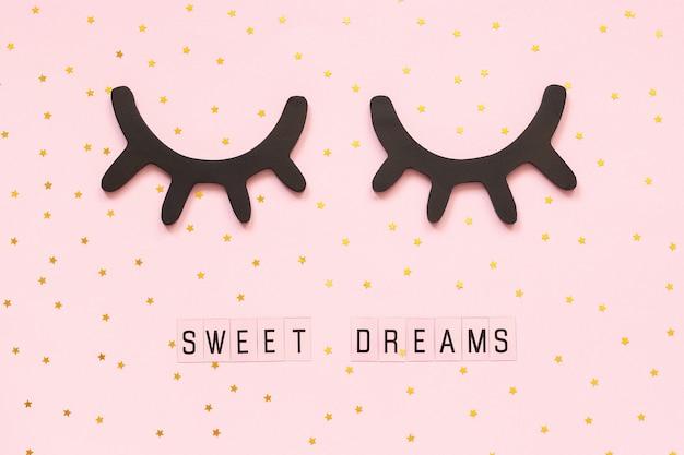 Süße träume des textes und dekorative hölzerne schwarze wimpern, geschlossener augengoldstern auf rosa hintergrund. Premium Fotos