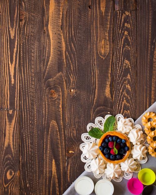 Süße weiße meringe und andere komponenten auf einem hölzernen hintergrund ,. Premium Fotos