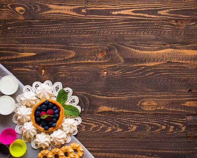 Süße weiße meringe und andere komponenten auf einem hölzernen hintergrund Premium Fotos