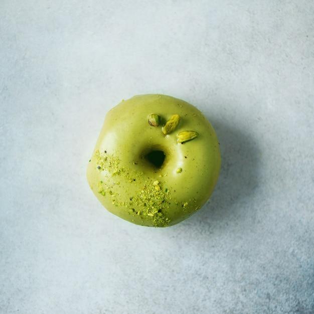 Süßer donut mit grüner glasur und pistazie auf grau. geschmackvoller donut auf konkreter pastellbeschaffenheit, kopienraum, draufsicht Premium Fotos