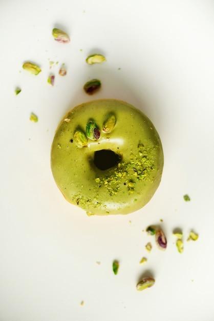 Süßer donut mit grüner glasur und pistazie auf grau. geschmackvoller donut auf konkreter pastellbeschaffenheit Premium Fotos