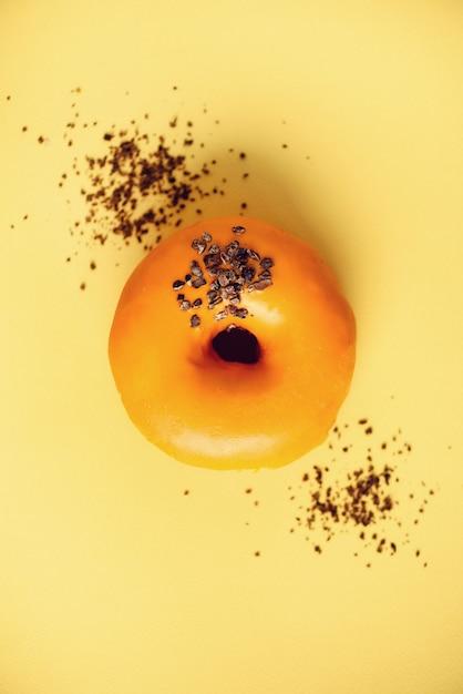 Süßer donut mit orange glasur und schokolade auf grau. geschmackvoller donut auf gelber pastellbeschaffenheit Premium Fotos