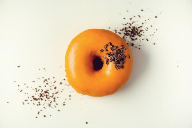 Süßer donut mit orange glasur und schokolade auf grau. geschmackvoller donut auf konkreter pastellbeschaffenheit Premium Fotos