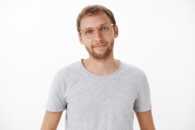Süßer freundlicher und gutaussehender männlicher europäer mit bart in brille und grauem t-shirt, das glücklich mit entspanntem und erleichtertem ausdruck lächelt, der kundenfrage über weißer wand hört Kostenlose Fotos