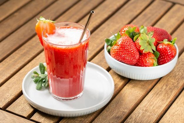 Süßer frischer erdbeersaft auf holztisch. gesundes essen Premium Fotos