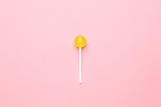 Süßer gelber süßigkeitslutscher auf pastellrosa. minimalistische komposition. Premium Fotos