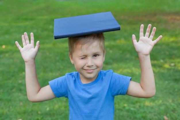 Süßer junge sitzt im gras in einem park und hält ein buch auf dem kopf und zwinkert einem auge zu. Premium Fotos