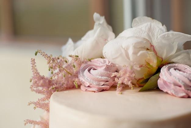 Süßer weißer sahnekuchen rund mit rosa rosenblüten und weißer pfingstrose oben drauf Premium Fotos