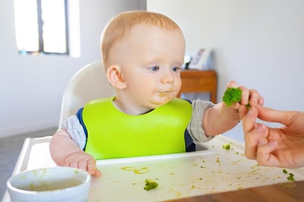 Süßes baby im lätzchen, das brokkoli-stück von mutter nimmt Kostenlose Fotos