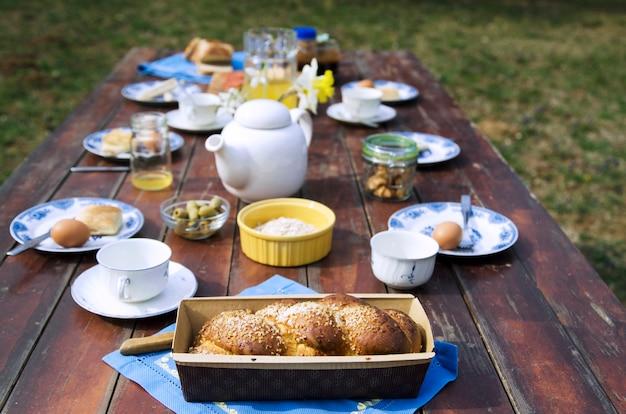 Süßes brot und frühstücksnahrung auf holztisch im hausgarten. Premium Fotos
