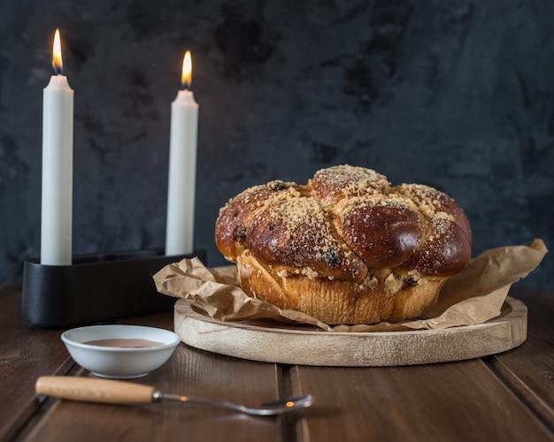 Süßes challah-brot auf einer bewaldeten runden platte auf hölzerner brauner tabelle mit honig und zwei kerzen an dem shabbat-abend, der kidush macht Premium Fotos