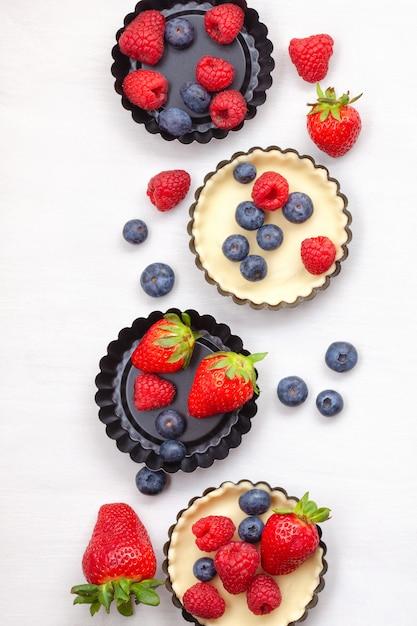 Süßes gebäck mit beeren backen. draufsicht, für rezept, kochkurse, kochblog. Premium Fotos