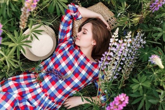 Süßes mädchen schläft in einem wiesengras voller lupinenblumen. Kostenlose Fotos