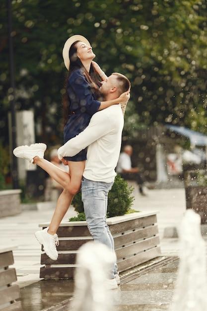 Süßes paar in einer stadt. mann in einem weißen hemd. die leute gehen. Kostenlose Fotos