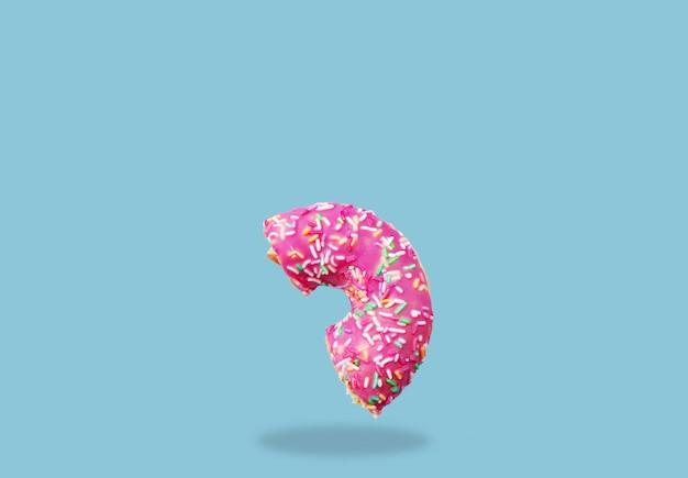 Süßes rosa schnitt donutfliege in einer luft auf blauem hintergrund Premium Fotos
