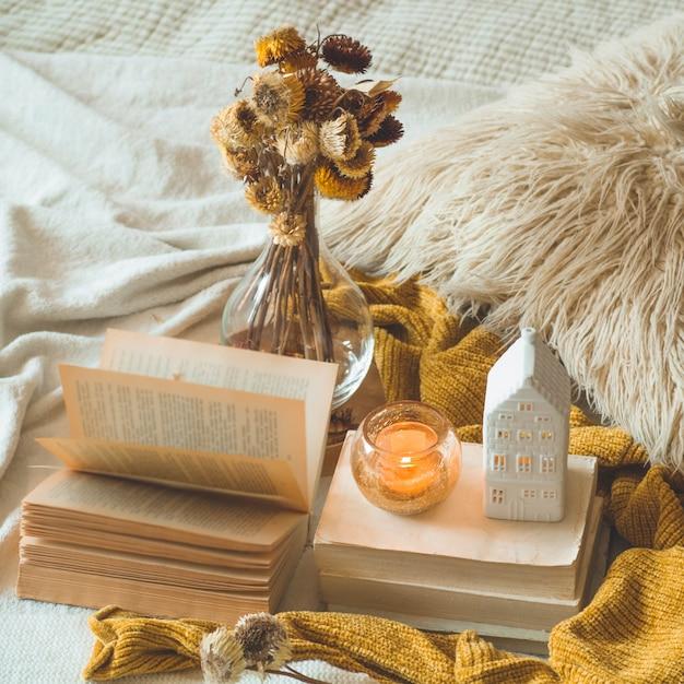 Süßes zuhause. stillleben details im innenraum des wohnzimmers. getrocknete blumenvase und kerze, herbstdekor auf den büchern. lesen, ausruhen. gemütliches herbst- oder winterkonzept. Premium Fotos