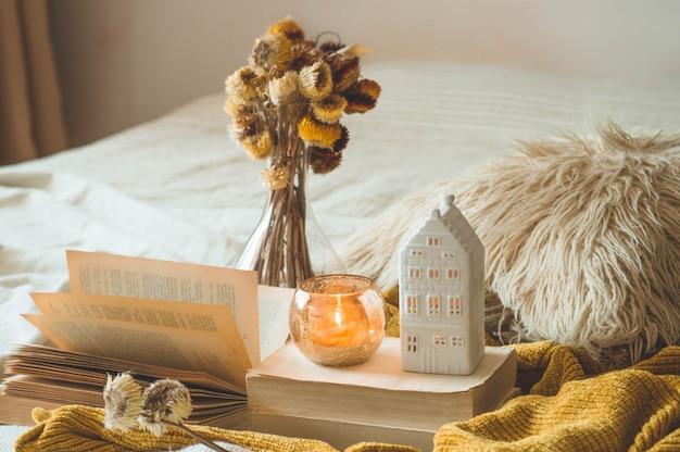 Süßes zuhause. stilllebendetails im hauptinnenraum des wohnzimmers. trockenblumenvase und kerze, herbstdekor auf den büchern. lesen sie, rest. gemütliches herbst- oder winterkonzept. Premium Fotos