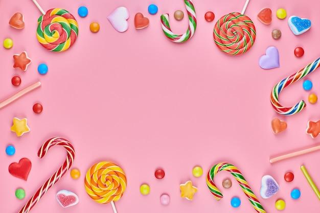 Süßigkeiten auf einem rosa hintergrund Premium Fotos