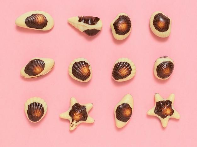 Süßigkeiten aus weißer und dunkler schokolade auf rosa gestapelt Premium Fotos