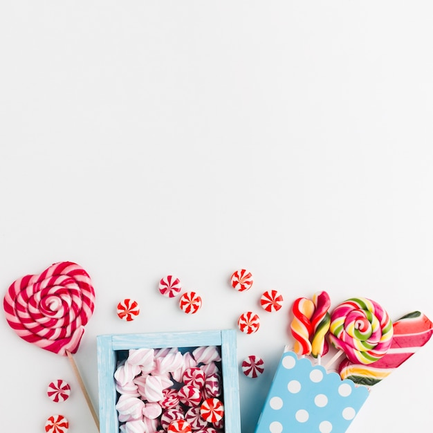 Süßigkeiten und lutscher auf weißer tabelle mit kopienraum Kostenlose Fotos