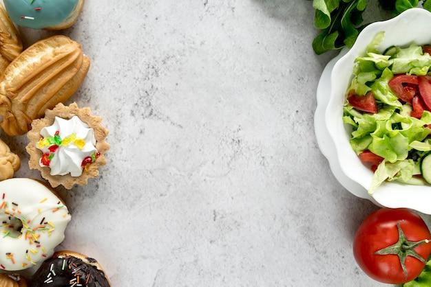 Süßwarenlebensmittel und gesunder gemüsesalat auf rauer oberfläche Kostenlose Fotos