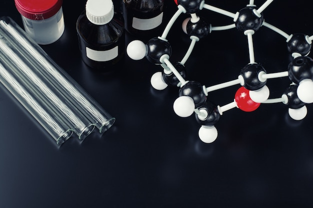 Summenformel und laborausstattung auf einem dunklen hintergrund. konzept der organischen chemie der wissenschaft Premium Fotos