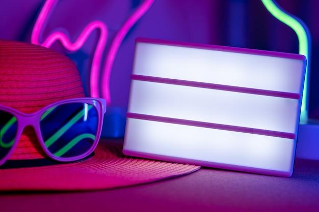 Summerblank-leuchtkasten auf hut mit sonnenbrille refection neonrosa und blaues und grünes licht auf tabelle Premium Fotos