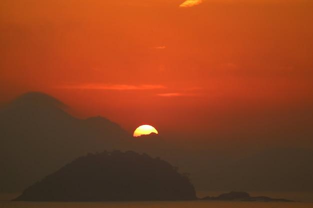 Sun, der von der wolkenschicht über dem atlantik-blick vom copacabana-strand in rio de janeiro steigt Premium Fotos
