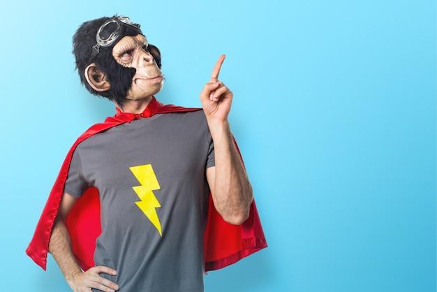 Superheld affe mann zeigt auf bunten hintergrund Premium Fotos