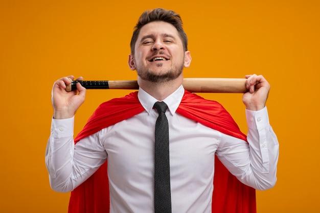 Superheld-geschäftsmann im roten umhang, der baseballschläger auf den schultern hält, die zuversichtlich über orange wand stehend lächeln Kostenlose Fotos