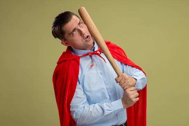 Superheld geschäftsmann im roten umhang, der sich mit baseballschläger schlägt, der über hellem hintergrund steht Kostenlose Fotos