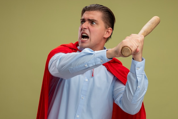 Superheld-geschäftsmann im schwingenden baseballschläger des roten umhangs mit aggressivem ausdruck, der über hellem hintergrund steht Kostenlose Fotos